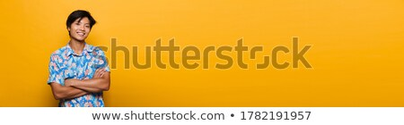 happy young asian man posing isolated over yellow background take a selfie showing copyspace stock photo © deandrobot
