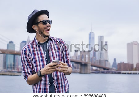 Happy bearded man in shirt and headphones listening music Stock photo © deandrobot