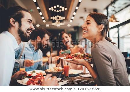 happy friends eating at bar or restaurant Stock photo © dolgachov