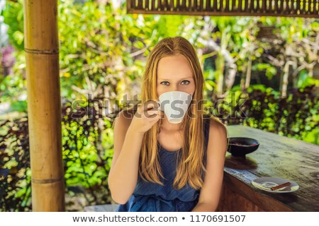 Young woman drinks coffee Luwak in the gazebo Stock photo © galitskaya