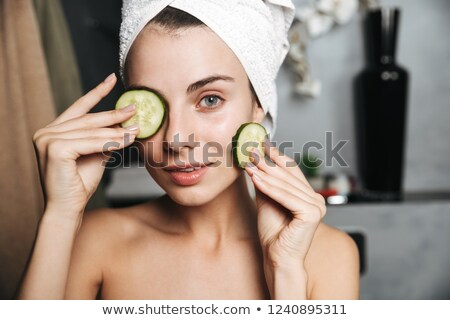Photo of attractive woman with towel on head holding cucumber sl Stock photo © deandrobot