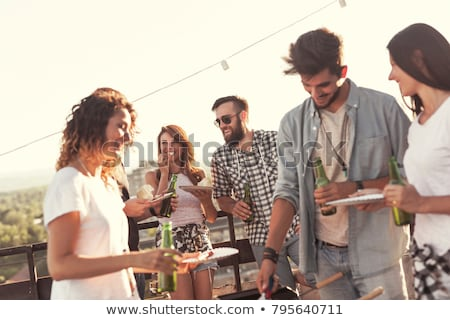 friends at barbecue party on rooftop in summer stock photo © dolgachov