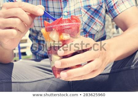 Jonge man eten vruchtensalade buitenshuis jonge Stockfoto © nito