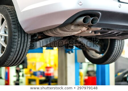 Car undergoing repair or a service in a workshop with focus to the exhaust pipe Stock photo © Lopolo