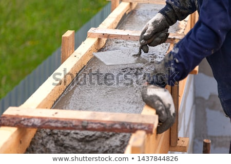 Construction Worker Using Wood Trowel On Wet Cement Forming Copi Stock photo © feverpitch