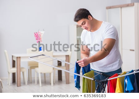 man hanging clothes on a drying rack