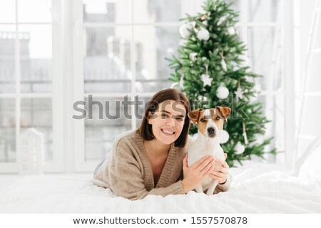 Love and care to pet. Pretty adult woman with short hairstyle, toothy smile, embraces her favourite  Stock photo © vkstudio