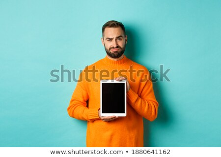 Disappointed and skeptical handsome masculine man in orange t-shirt cringe feeling awkward and indec Stock photo © benzoix