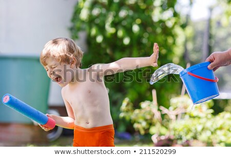 Cute little boy playing in the kiddy pool. Stock photo © rcarner