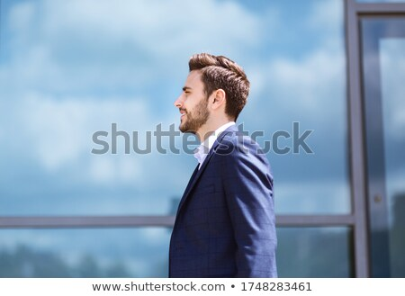 Outdoor view of handsome attractive male executive or CEO in formal suit, stans crossed legs near co Stock photo © vkstudio