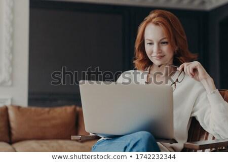 Horizontal shot of happy skilled ginger woman teacher works distantly, checks students works via lap Stock photo © vkstudio