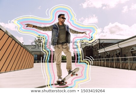 indian man doing trick on skateboard on roof top Stock photo © dolgachov