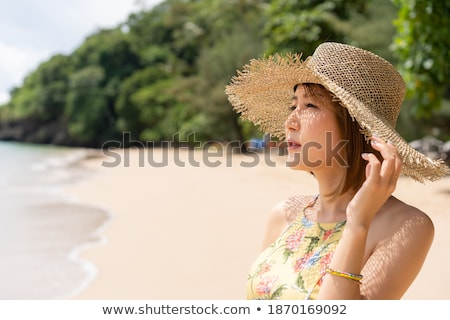 Beautiful attractive young woman standing at the beach, admiring Stock photo © HASLOO