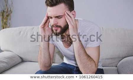 young man holds head while sitting stock photo © feedough