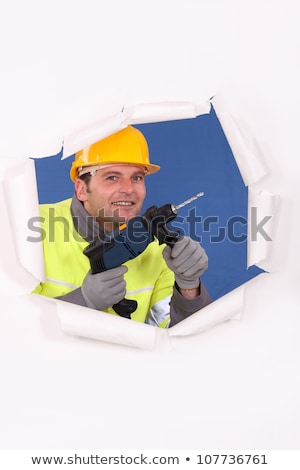 Manual worker with drill tearing through poster Stock photo © photography33