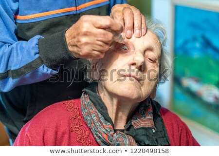 Woman putting eyewash in eyes of a man stock photo © photography33