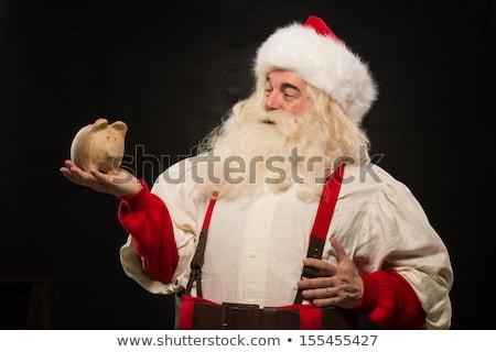 Santa Claus holding piggy bank moneybox Stock photo © HASLOO