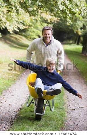 father giving son ride in wheelbarrow stock photo © monkey_business