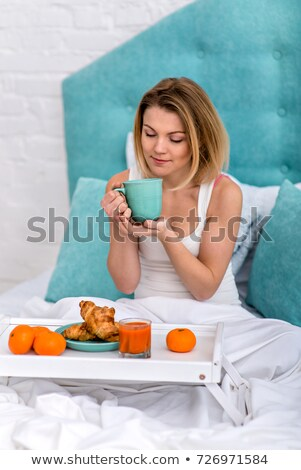 Stock photo: Beautiful woman savoring a cup of coffee in bed