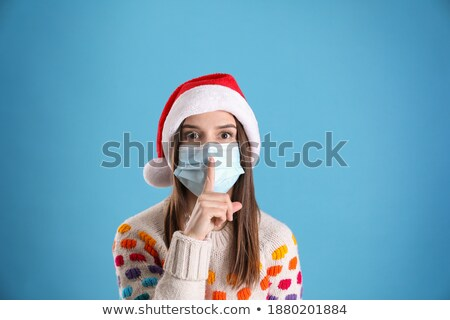 christmas woman wearing a santa hat showing silence gesture stock photo © hasloo