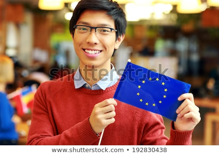 cheerful asian boy in glasses holding flag of europe union stock photo © deandrobot