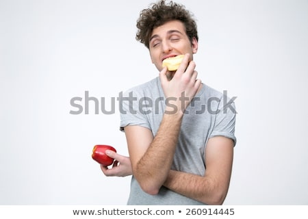 Young man holding apple and eating unhealthy donut Stock photo © deandrobot