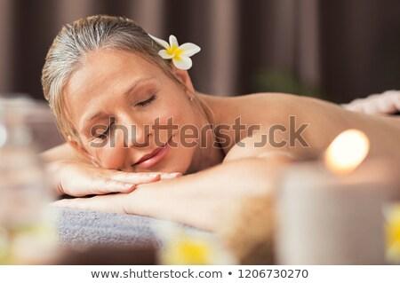 Woman resting on massage lounger Stock photo © deandrobot