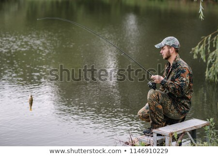 Fisherman standing on a river bank. Stock photo © IS2