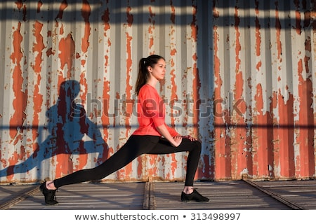 young caucasian woman in sport wear stretching her leg before wo stock photo © deandrobot