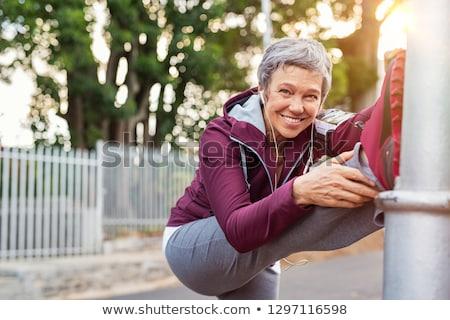 Nő nyújtás lábak mosolyog kamerába portré Stock fotó © IS2