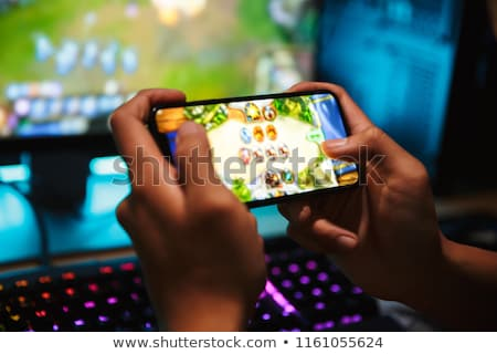 Hands of young gamer boy playing video games on smartphone and c Stock photo © deandrobot