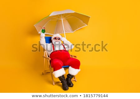 Stock photo: santa claus sitting in a deckchair on the beach