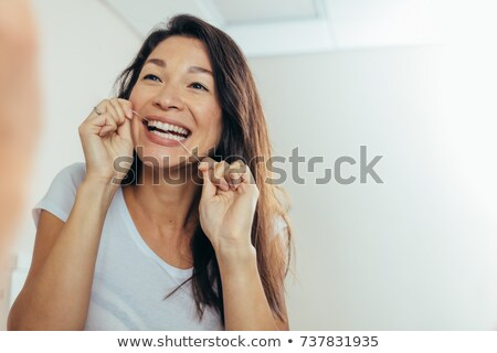 Woman Flossing Her Teeth Stock photo © AndreyPopov