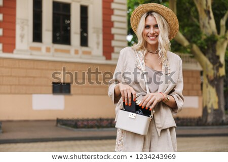 image of young lady wearing suit and straw hat putting mobile ph stock photo © deandrobot