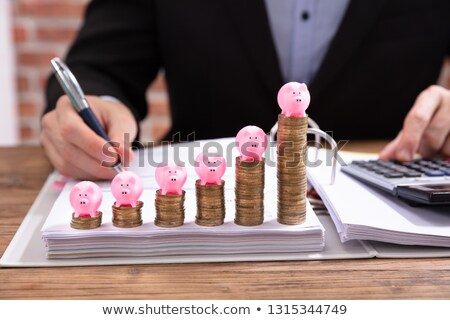Stock photo: Pink Piggybank Over Stacked Coins
