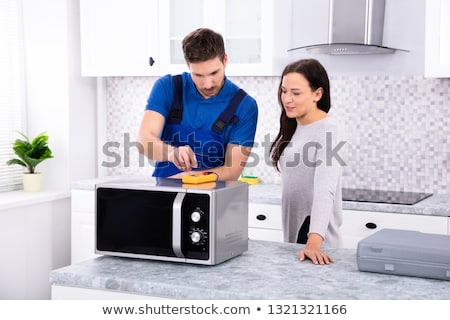 Male Repairman Repairing Oven In Kitchen Stock photo © AndreyPopov