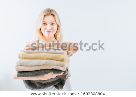 A woman is holding a stack of white towels. Concept of service in hotels, laundry, spa ストックフォト © galitskaya