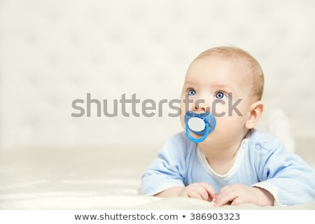 A cute baby with pacifier lying on a white bed Foto stock © Lopolo