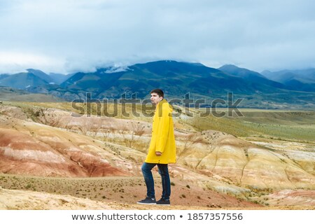 Young man in yellow jacket with backpack in mountain valley Stock photo © denbelitsky