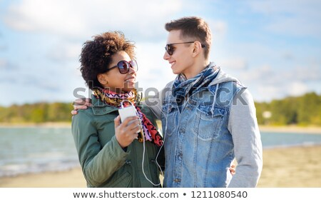 couple with smartphone and earphones over beach Stock photo © dolgachov