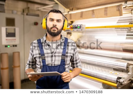 Young professional in headphones using touchpad while doing quality control work Stock photo © pressmaster