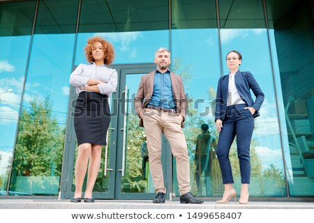 Row of young elegant office managers standing by entrance of office building Stock photo © pressmaster
