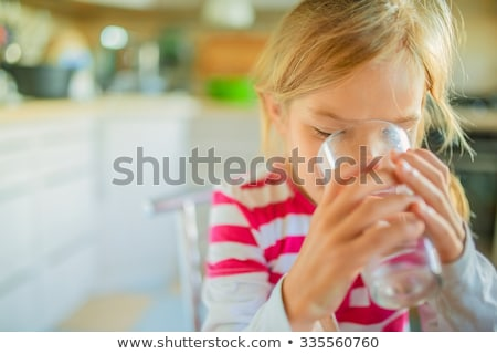 Teenager girl drinking water in the kitchen Stock photo © Lopolo