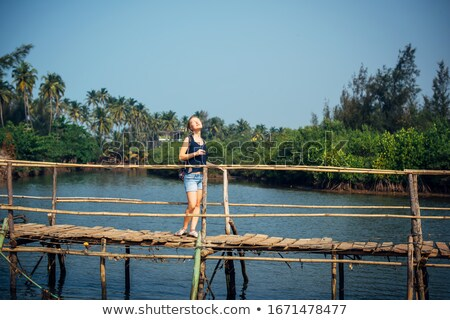A woman in denim shorts in summer stands in a small tourist boat parked at the pier Stock photo © ElenaBatkova