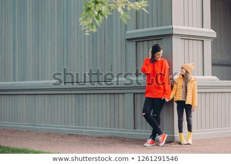 Horizontal view of fashionable European female in red loose sweater, ripped jeans, holds hands toget Stock photo © vkstudio