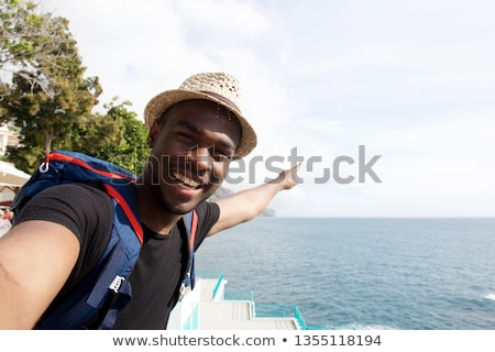 Image of african american guy smiling and pointing fingers at yo Stock photo © deandrobot