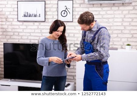 Technicien femme signature facture souriant client Photo stock © AndreyPopov