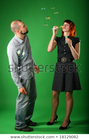 Girl with red hair blows soap bubbles, and guy looks at it stock photo © Paha_L