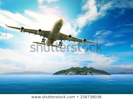 Airplane fly over land and ocean stock photo © Ansonstock