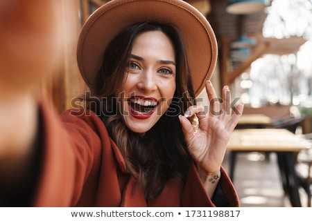 Closeup portrait of pretty woman sitting at cafe and signing doc Stock photo © HASLOO